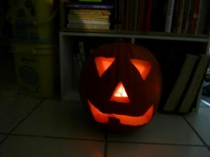 Traditional Jack o lantern with triangle eyes and nose, and a mouth with 1 tooth
